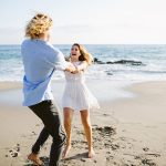 fun couple dances on beach