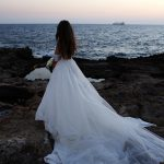 Bride's long dress by the water on the rocks