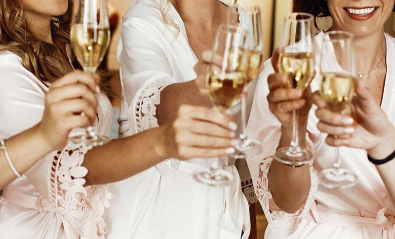 Bridesmaids in robes toasting champagne